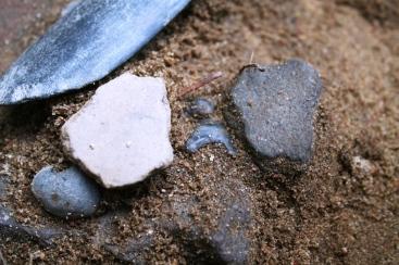 Fragmenty naczyń i krzemienny grot strzały złożone w jednym z odkrytych depozytów